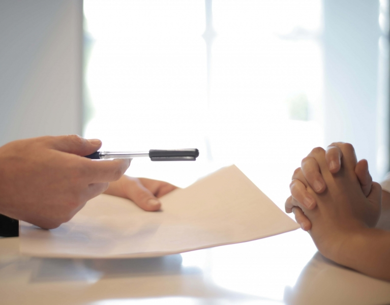 man passing contract to woman
