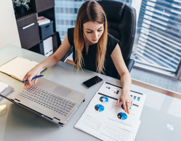woman at a desk looking at paperwork