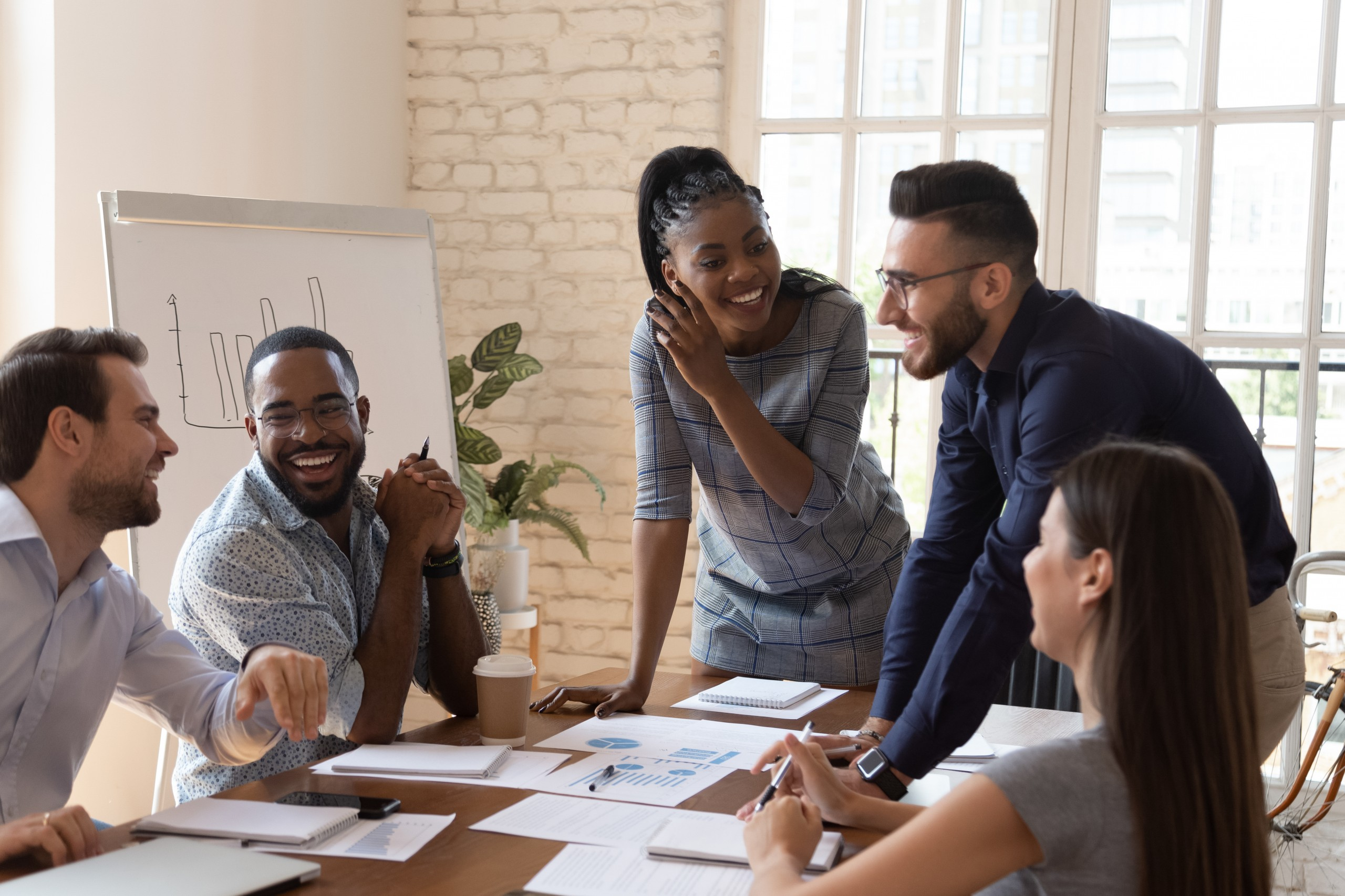 Employees at meeting around desk talking and laughing
