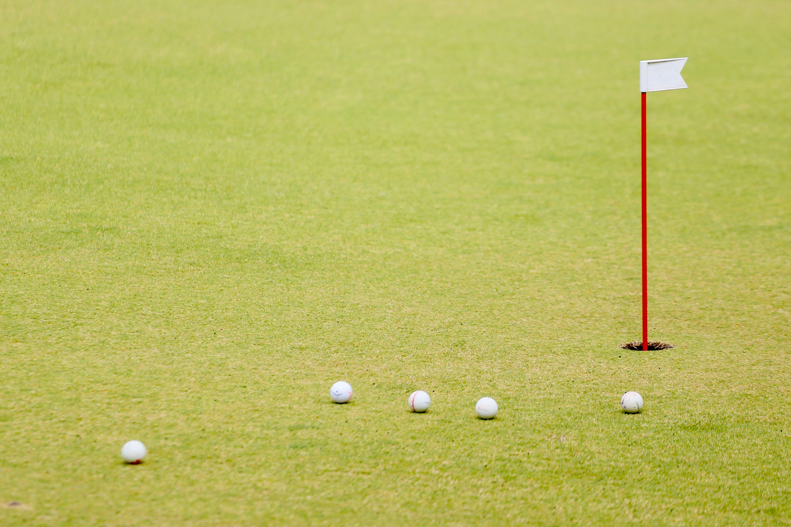 five golf balls rest next to a hole with a small flag