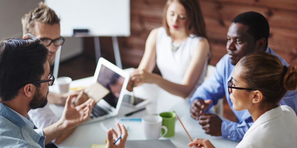 a team of five people have a meeting around a conference table